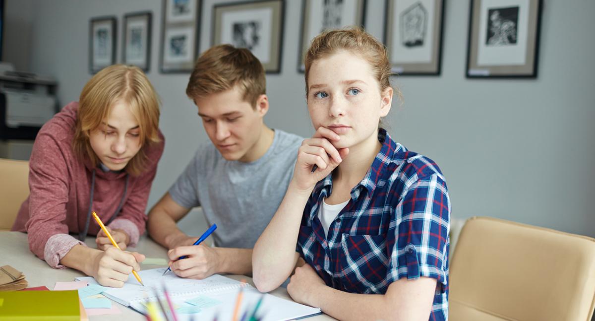 Tre ungdommer gjør gruppearbeid på skolen.