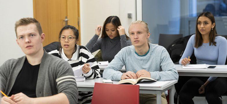 Elever ved pultene i klasserommet.