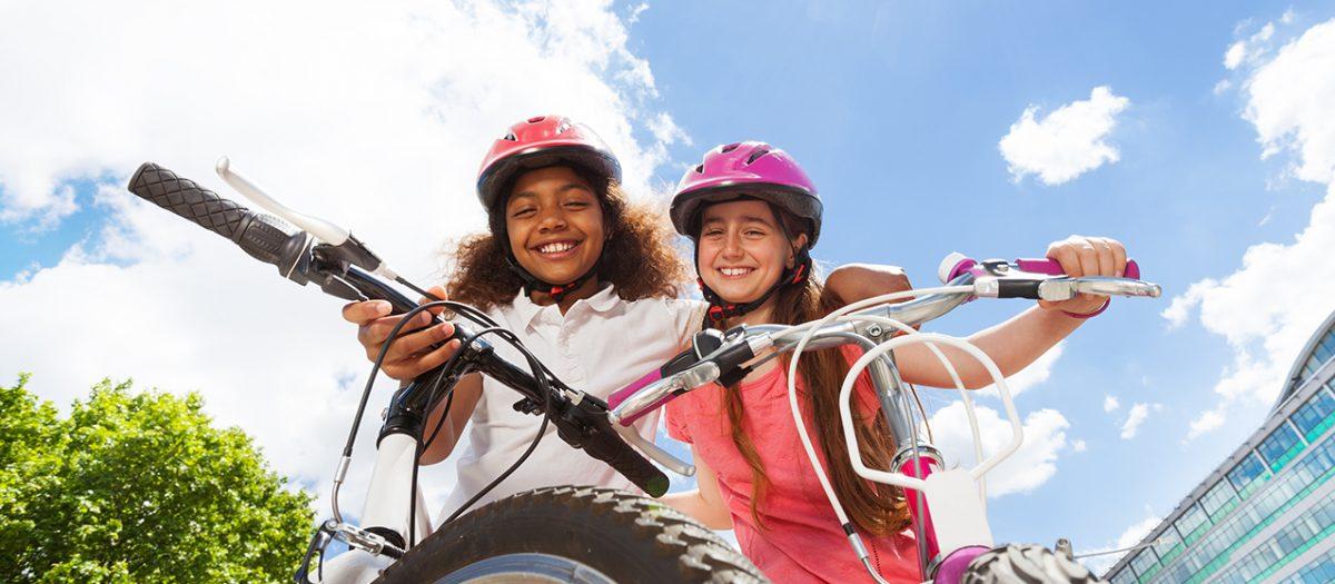 Jenter på sykkel ute i byen