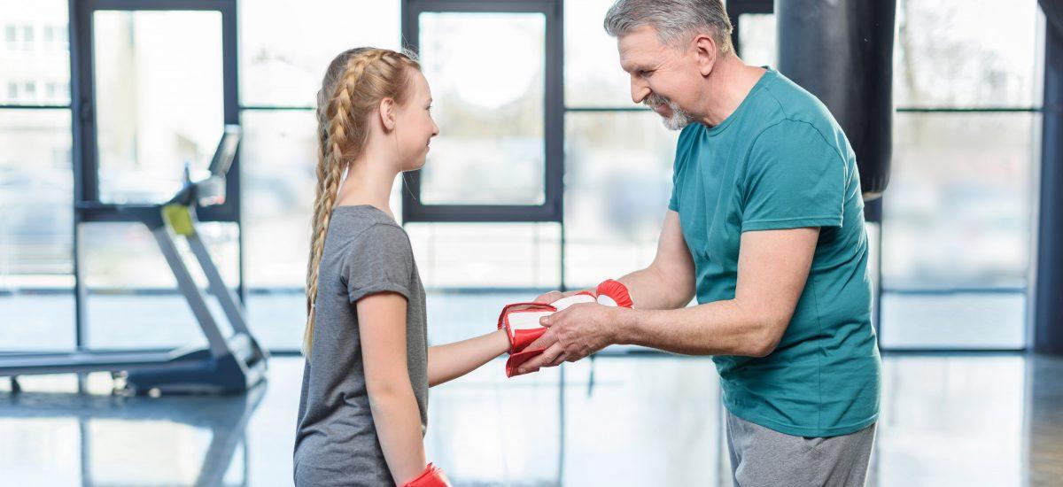Ung jente i boksestudio får hjelp med hanskene av far/trener.