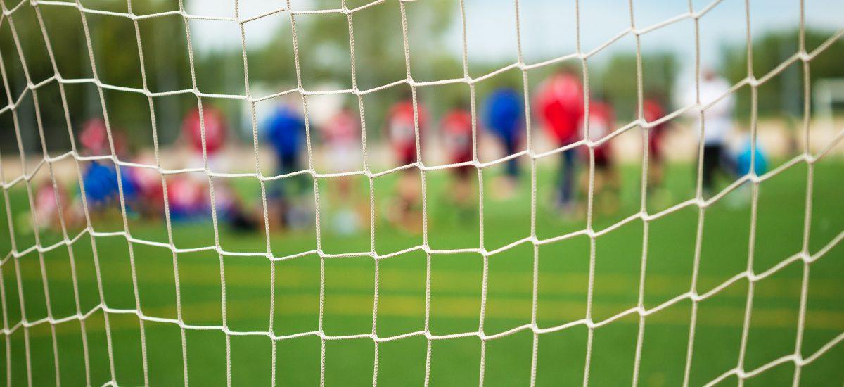 Utydelige fotballspiller sett gjennom målnettet.