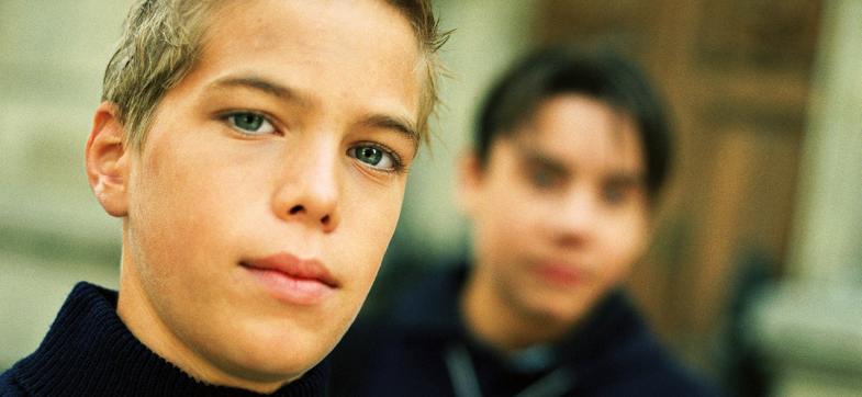 To unge gutter med mørke klær ser i kamera. Foto: colourbox.com