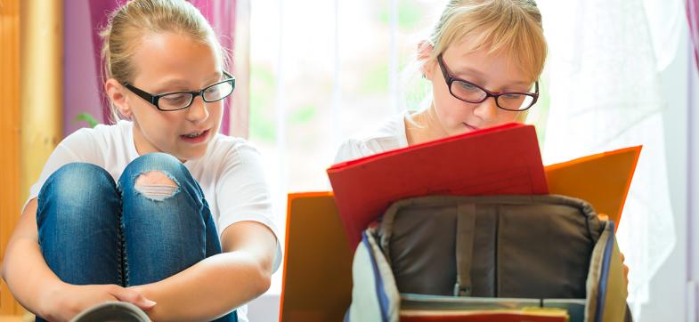 Tvillinger med skolesekk og lekser. Foto: colourbox.com