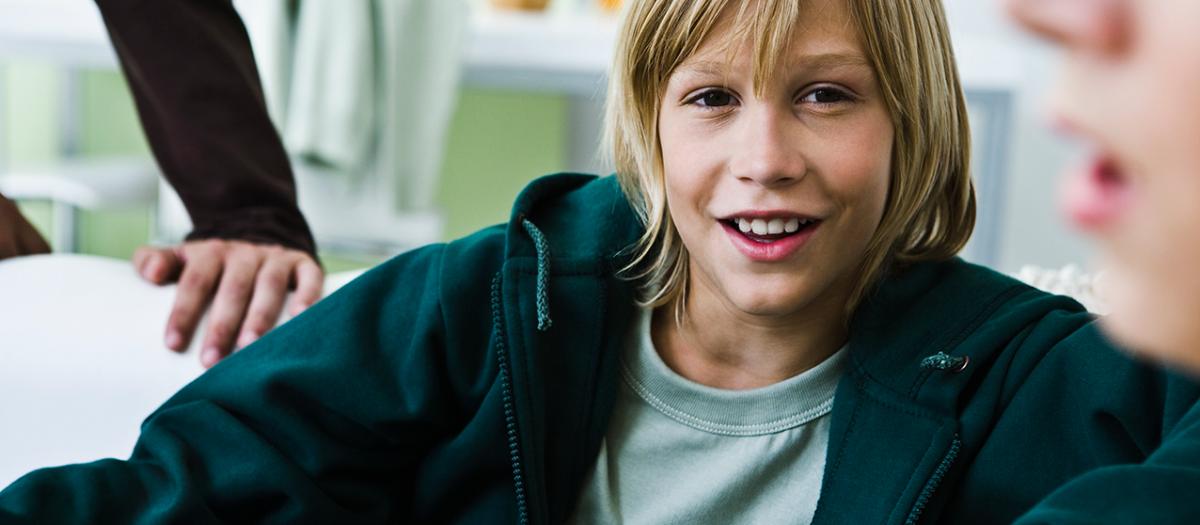 12-årig gutt på gutterommet, med langt hår, ser i kamera. Foto:colourbox.com