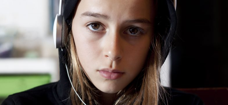 Alvorlig ungdom med høretelefoner og lue ser i kamera. Foto: colourbox.com