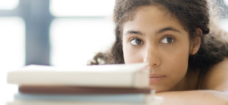 Jente ligger over pulten og ser i kamera. Krøllete, mørkt hår. Foto: colourbox