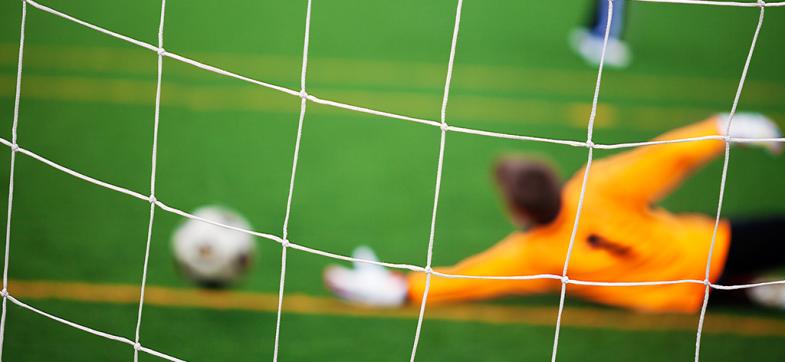 Målvakt på fotballbane slenger seg etter ball. Foto tatt bakfra. Foto: colourbox.com