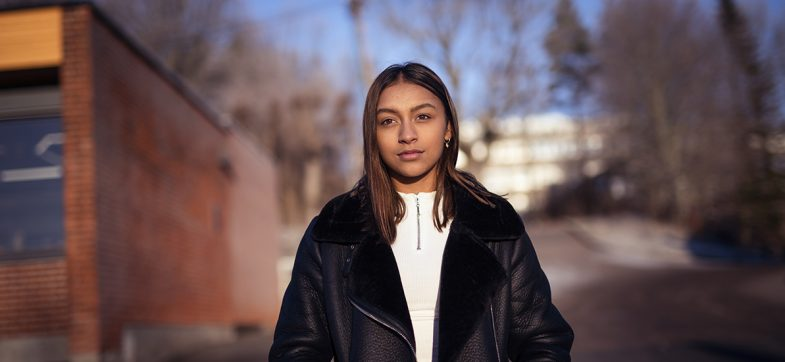 Ung jente med langt mørkt hår ute foran en skole.