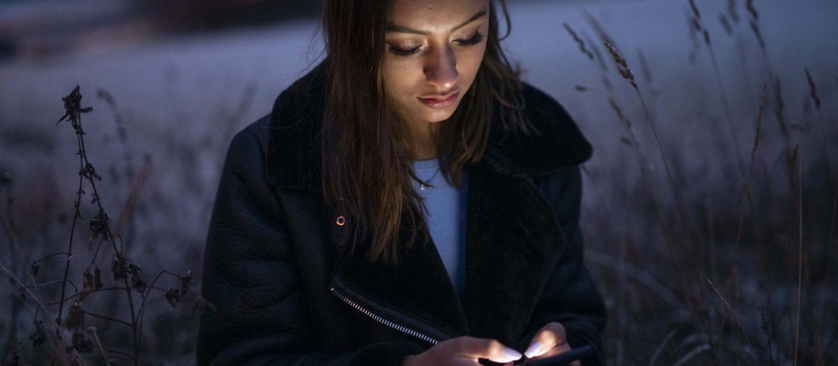 Ung jente sitter ute i mørket og ser ned på mobil som lyser. Foto: S.B. Vold / Ungdata
