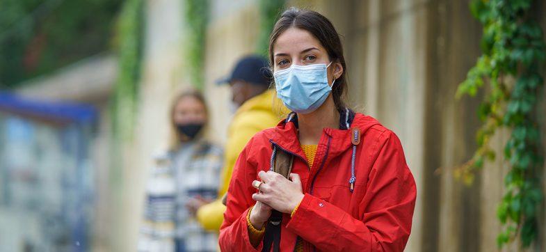 Ungdom, jente, står i gaten med rød jakke og munnbind.