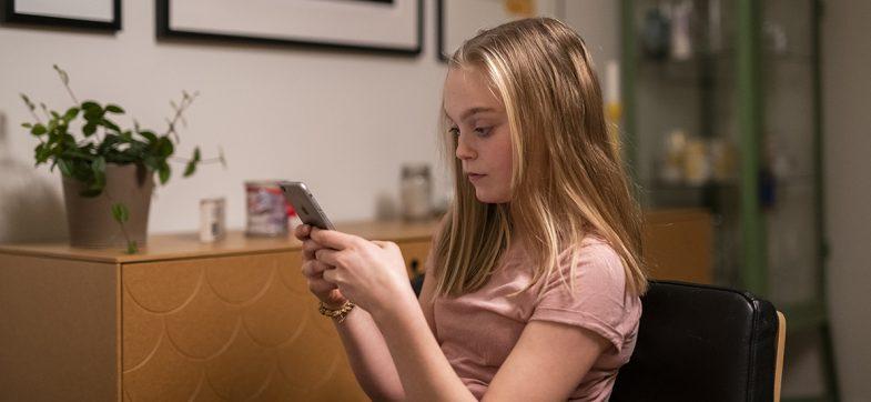 Ung jente ser på mobilen hjemme i stuen.