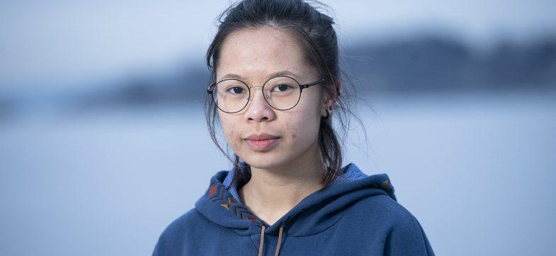 Portrett av ung jente med runde briller og mørkt hår i hestehale ute.